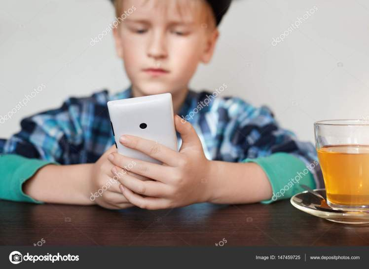 A little schoolboy dressed in checked shirt siting at wooden table with a cup of tea holding smartphone in his hands. People, technology, lifestyle and internet concept