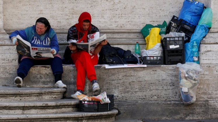 Homeless man and woman read newspapers as they sit in front of church in downtown Rome