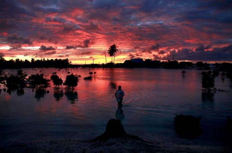 A villager wades through a small lagoon near the village of Tangintebu on South Tarawa in the central Pacific island nation of Kiribati