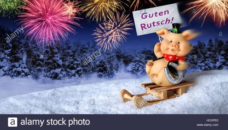 lucky-pig-su-di-una-slitta-tenendo-un-cartello-che-diceva-guten-rutsch-tedesco-per-felice-anno-nuovo-con-fuochi-dartificio-nel-cielo-notturno-hcxpe0